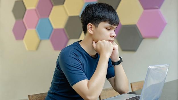 Concetto di studio online l'uomo che indossa una camicia blu scuro seduto sulla sedia di legno e cerca di uscire da un'idea creativa da aggiungere al suo nuovo progetto.