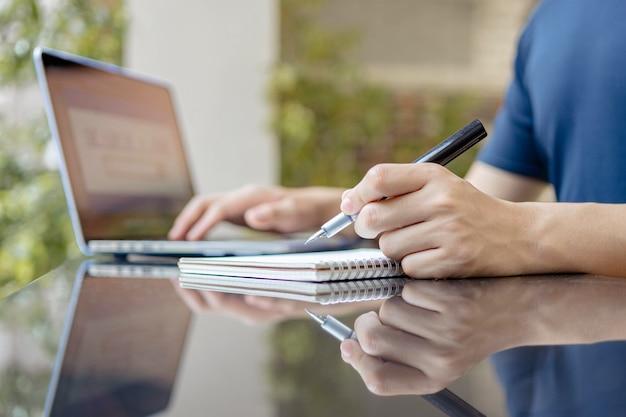 Concetto di studio online l'uomo che sta lavorando da casa tentando di scrivere il rapporto della riunione mentre sta conducendo la riunione online della sua azienda.