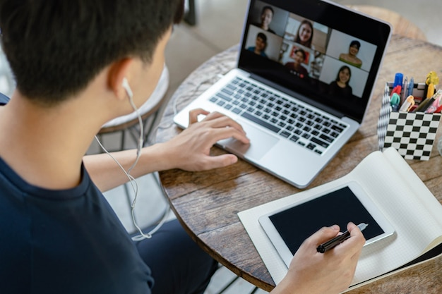 Concetto di studio online il giovane uomo dell'azienda che mette un computer portatile sul tavolo di legno essendo impegnato a fare la lista di controllo sul libro scrivendola sul suo dispositivo tecnologico.
