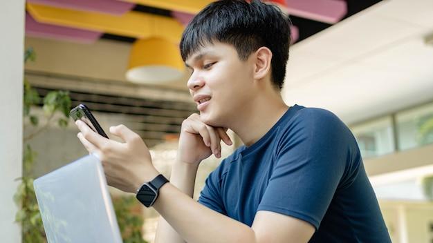 Concetto di studio online il giovane in maglietta blu intenso e orologio nero che usa il suo smartphone per chiamare i suoi amici perché al momento non si presentano alla riunione online.