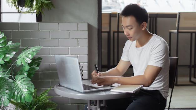 Concetto di studio online il giovane in semplice maglietta bianca e pantaloni neri che lavora usando il suo computer portatile per cercare informazioni secondo i brevi concetti scritti sul taccuino.