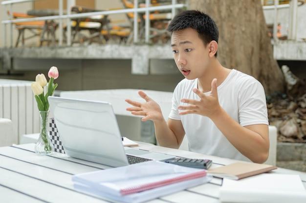 Concetto di studio online il giovane studente online che fissa il suo laptop con la mano sulla testa, sembra stressato e ansioso per il punteggio dell'esame.