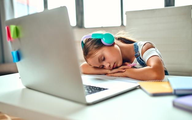 Formazione on line. una bambina con le cuffie si è addormentata mentre ascoltava una lezione su un laptop. scuola a casa tra pandemia e quarantena.