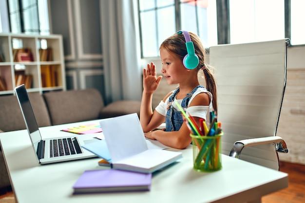Formazione on line. la ragazza del bambino in cuffie ascolta una lezione su un computer portatile. scuola a casa tra pandemia e quarantena.