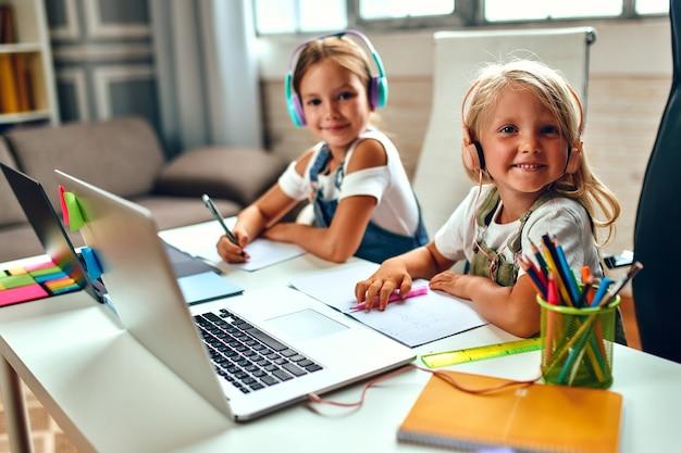 Formazione on line. due sorelle della scolaretta in cuffia ascoltano le lezioni sui computer portatili. scuola a casa tra pandemia e quarantena.