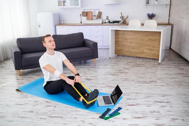 Formazione on line. giovane che fa esercizio con elastici fitness con tutorial online a casa, spazio libero. fare sport in casa