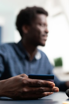 Consumatore di transazioni online che acquista con carta di credito introducendo dati di pagamento uomo afroamericano ma...
