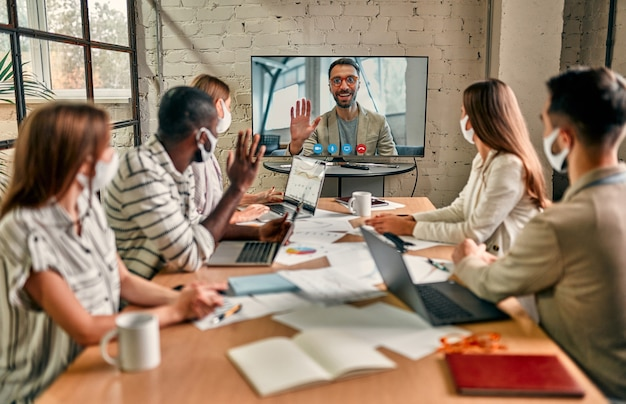 Formazione video online con videoconferenza e team aziendale per covid-19. uomini d'affari che indossano maschera facciale, si incontrano, discutono, scambiano idee per investire in ufficio durante il coronavirus