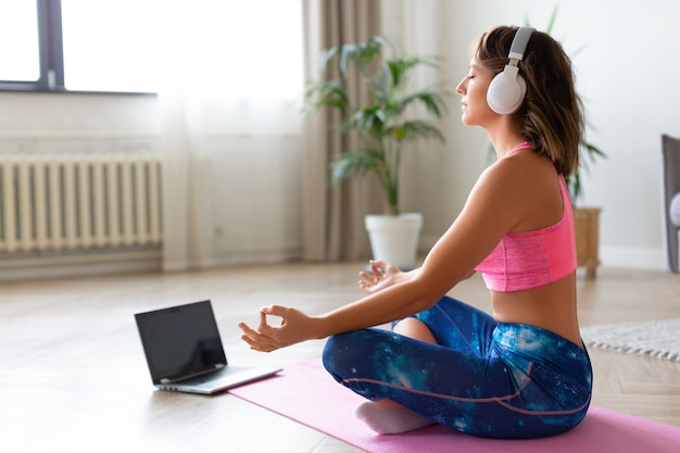 Lezione di yoga online. donna in cuffia nella posizione del loto davanti al monitor del laptop.