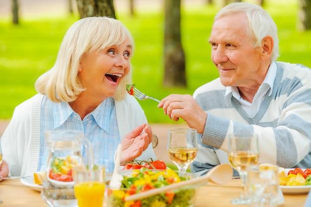 Solo il meglio per i nostri più vicini. uomo anziano che alimenta la sua allegra moglie con insalata fresca mentre entrambi sono seduti al tavolo da pranzo all'aperto
