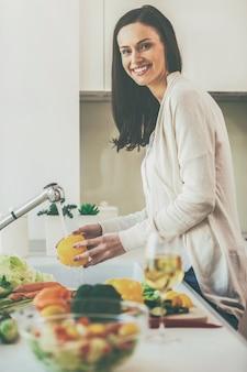 Solo verdure pulite e fresche per la mia insalata. bella giovane donna che lava le verdure per l'insalata e sorride mentre sta in piedi in cucina