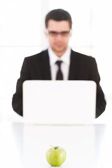 Solo idee fresche. fiducioso giovane in abiti da cerimonia che lavora al computer mentre è seduto al suo posto di lavoro con una mela verde in primo piano