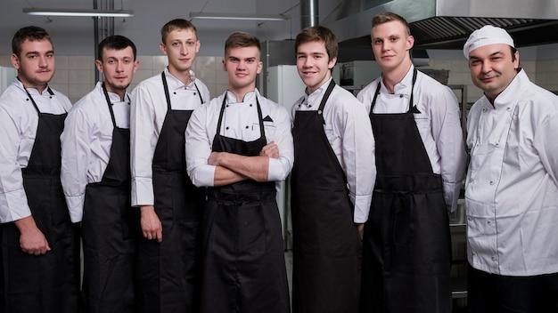 Solo uno diventerà sous chef. cuochi maschi in piedi nella cucina di un ristorante prima del colloquio di lavoro