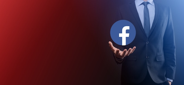 Onok, ucraina - luglio 14,2021: l'uomo d'affari tiene, fa clic, l'icona di facebook nelle sue mani. rete sociale. rete globale e connessione cliente dati. rete internazionale.
