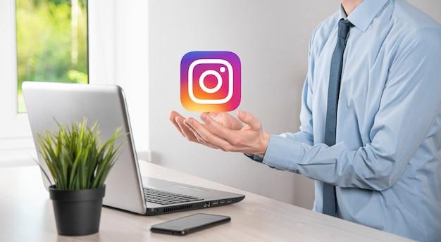 Onok, ucraina - luglio 14,2021: l'uomo d'affari tiene, fa clic, icona di instagram nelle sue mani. rete sociale. rete globale e connessione cliente dati. rete internazionale.