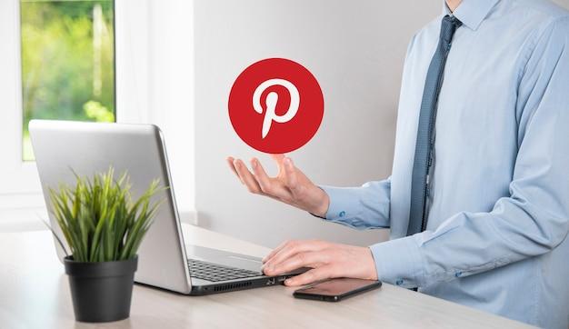 Onok, ucraina - luglio 14,2021: l'uomo d'affari tiene, fa clic, icona di pinterest nelle sue mani. rete sociale. rete globale e connessione cliente dati. rete internazionale.