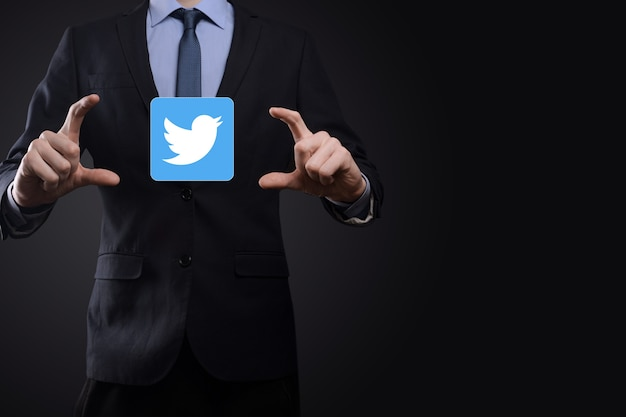 Onok, ucraina - luglio 14,2021: l'uomo d'affari tiene, fa clic, l'icona di twitter nelle sue mani. rete sociale. rete globale e connessione cliente dati. rete internazionale.