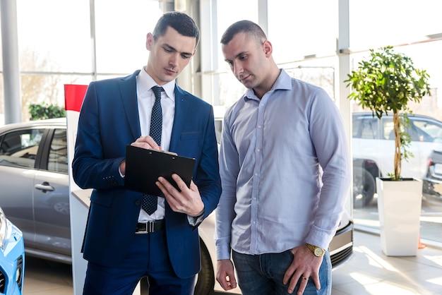 Un consulente firma i documenti con l'acquirente sull'auto