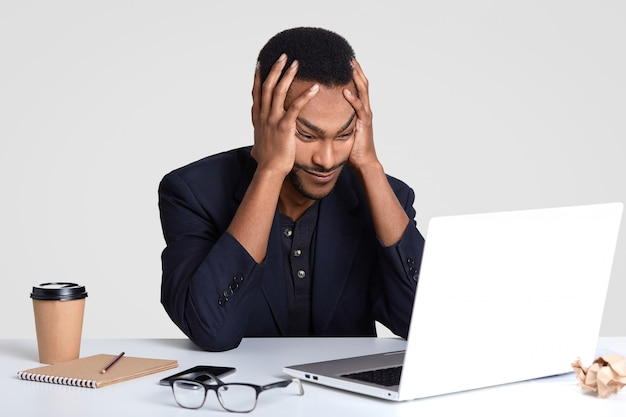 Un uomo stressante stanco e affaticato tiene le mani sulla testa, si diletta con perplessità, non sa come preparare la relazione finanziaria, indossa abiti formali, si concentra sul computer portatile portatile, scrive note