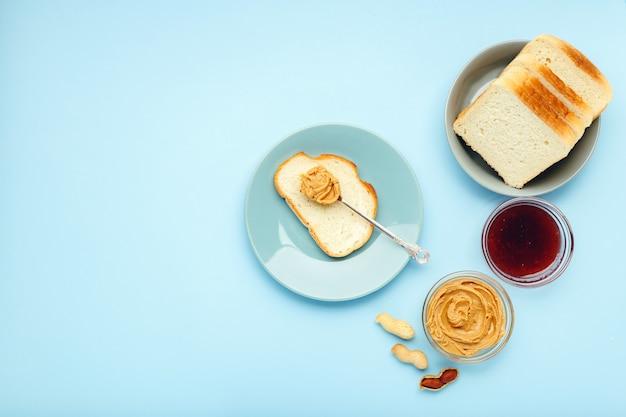 Cucinare la colazione spalmando il pane, toast con burro di arachidi, pasta di arachidi cremosa su sfondo di colore blu