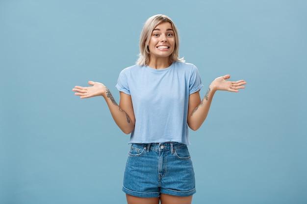 Ops non lo so. stupida ragazza europea carina con capelli biondi e bei tatuaggi che scrolla le spalle