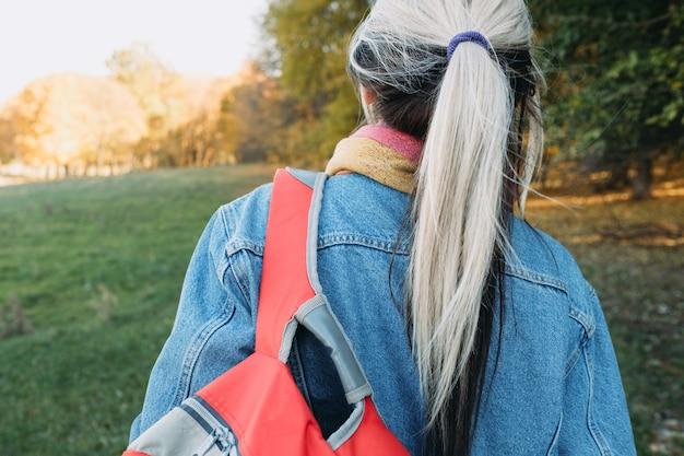 Tempo libero all'aria aperta vista posteriore della signora con lo zaino nel parco naturale di autunno