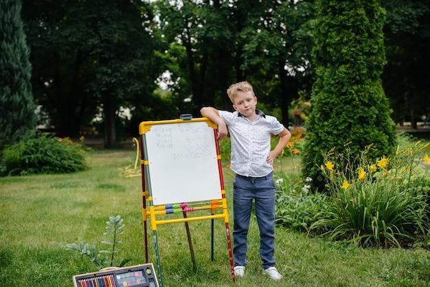 All'aria aperta, nel parco, uno studente scrive esempi alla lavagna. torna a scuola, studia durante la pandemia.