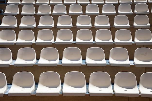 Teatro all'aperto con luce naturale; file di sedili in plastica