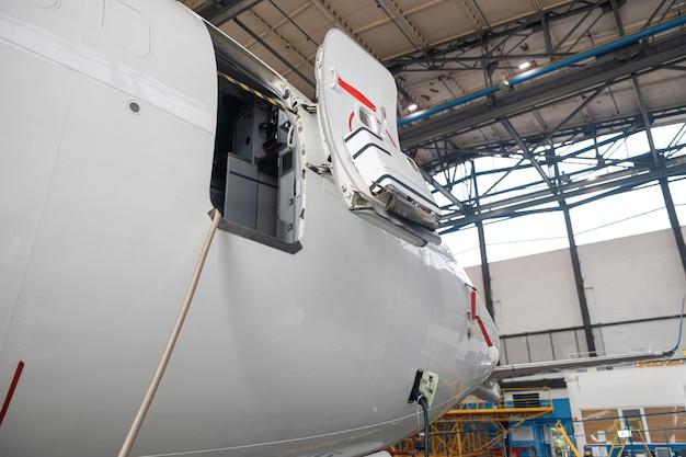 Aprire la porta dell'aereo e il cocpit. aereo passeggeri in riparazione di manutenzione nell'hangar dell'aeroporto al chiuso