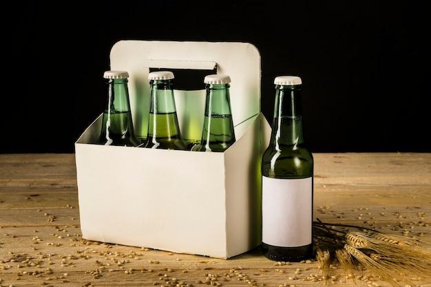 Una scatola di bottiglie alcoliche aperta e spighe di grano su venatura del legno