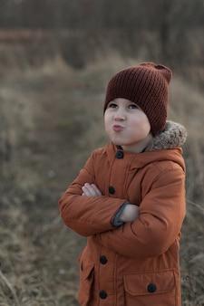 Apra il ritratto di autunno di un ragazzo carino vestito con una giacca marrone e un cappello, un bambino che si diverte nel parco.