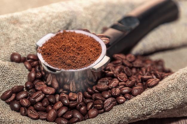 Un sacchetto aperto di chicchi di caffè. portafiltro con caffè macinato per macchine da caffè.