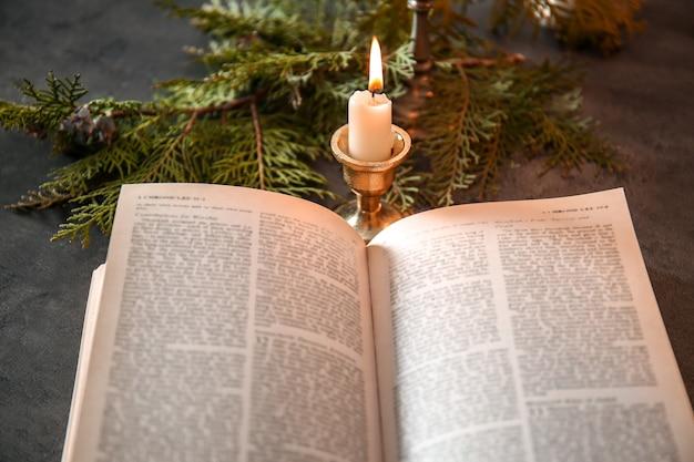 Bibbia aperta, candela e rami di conifere sul tavolo