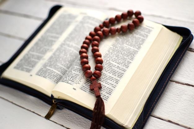 Bibbia aperta e rosario su un tavolo di legno bianco