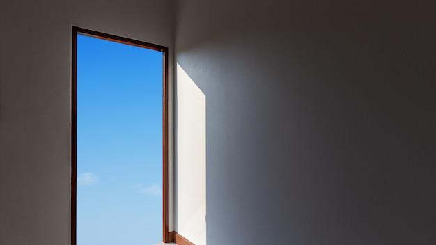 Apra la grande porta sulla parete contro cielo blu, concetto di speranza