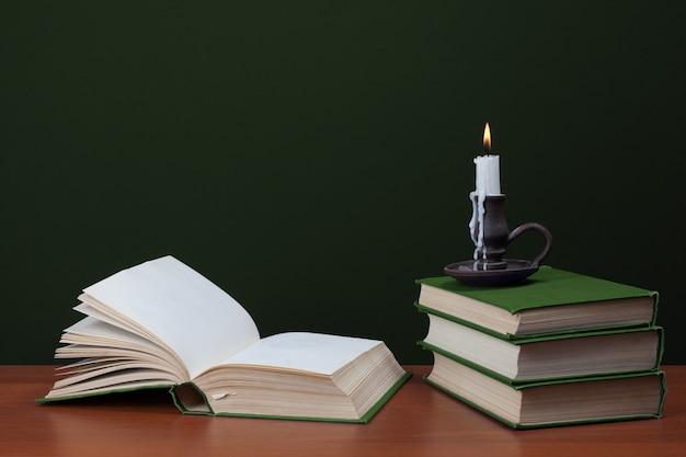 Libro bianco aperto e pila di vecchi libri con candele accese su sfondo verde. concetto di storia