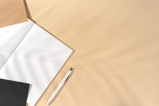 Apra il blocco note in bianco con lo spazio della copia su beige
