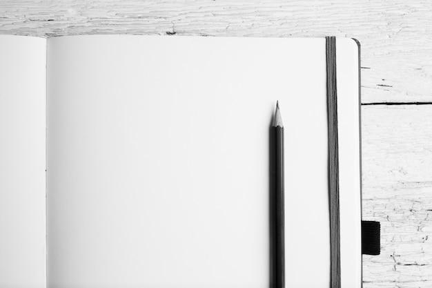 Apra il blocco note in bianco con le pagine vuote con una matita sulla tavola di legno bianca