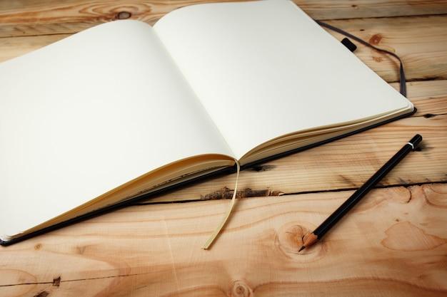 Apra il blocco note in bianco con le pagine bianche vuote che pongono su una tavola di legno