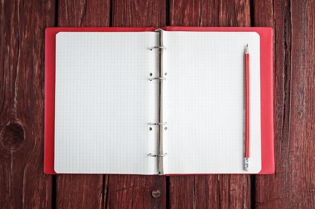 Apra il blocco note in bianco con una matita che pone sulla vecchia tavola di legno