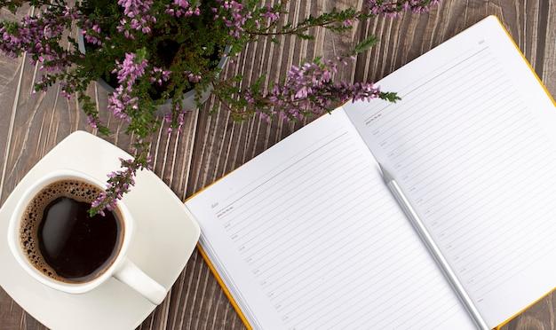 Apri un taccuino bianco vuoto, una penna e una tazza di caffè sullo sfondo di legno
