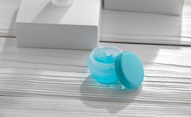 Aprire il contenitore di gel blu sul tavolo di legno bianco accanto alla finestra