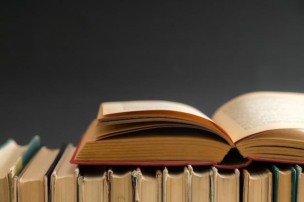 Libro aperto sulla superficie nera, libri con copertina rigida sulla tavola di legno.