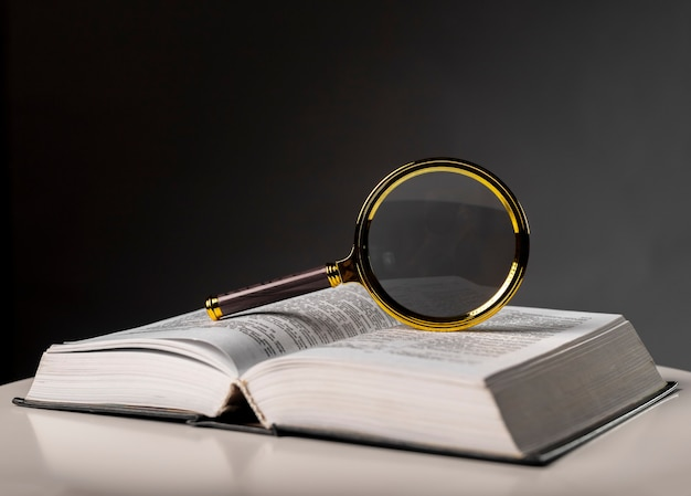 Primo piano del libro aperto con girare le pagine e lente d'ingrandimento. libro di testo in copertina rigida sul tavolo. studio e concetto di ricerca.