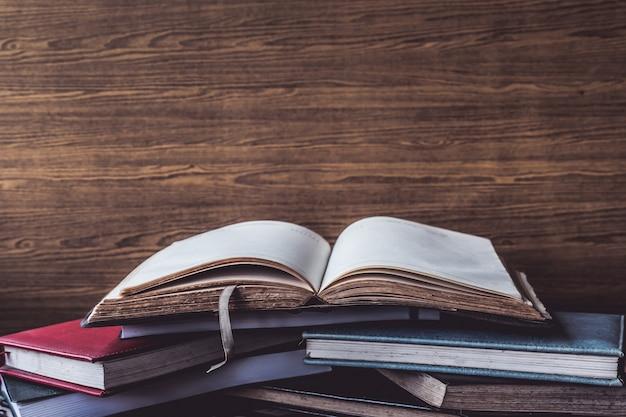 Libro aperto, libri con copertina rigida su fondo di legno della parete. spazio libero per il testo