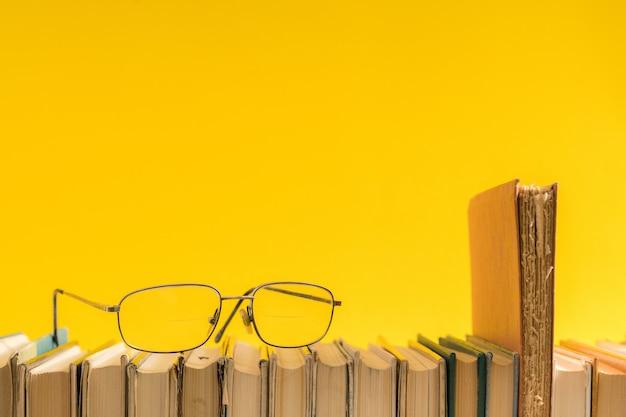 Libro aperto, libri con copertina rigida con copertina rigida e occhiali da lettura sul lato.