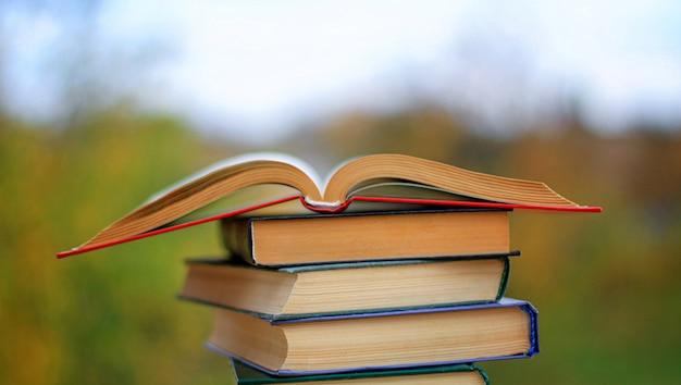 Un libro aperto che giace su una pila di libri su un tavolo di legno sullo sfondo del giardino.