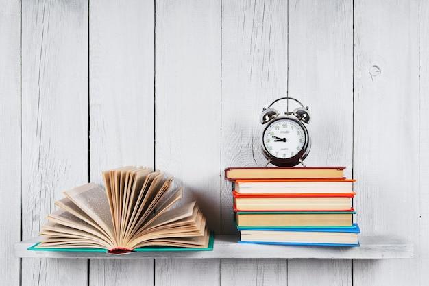 Il libro aperto, altri libri multicolori e la sveglia. su uno scaffale di legno.