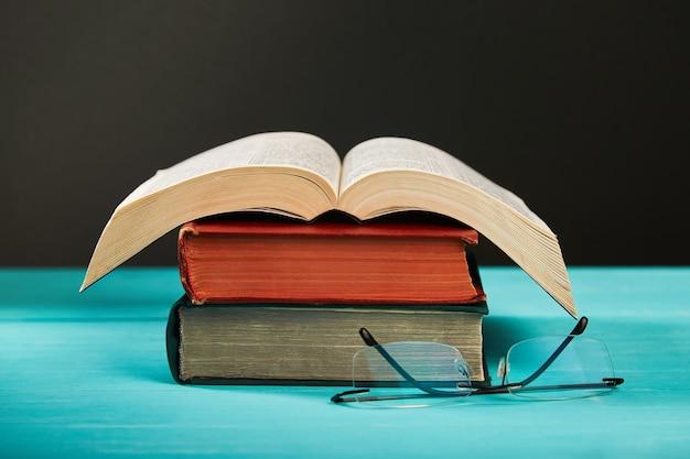 Libro aperto su una pila di libri su un tavolo.