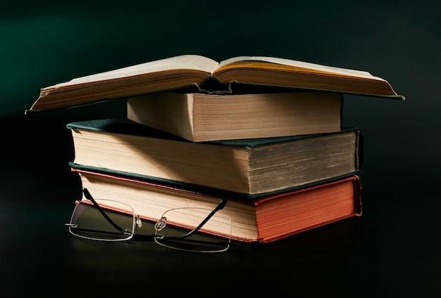 Libro aperto su una pila di libri sul tavolo